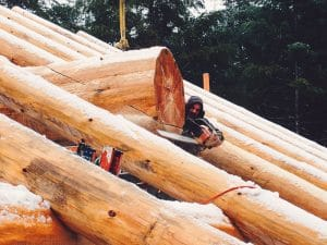 a logs home builder sawing off additional log on the roof