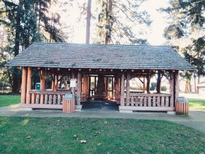 Front view of the log construction covered picnic area in park forest area