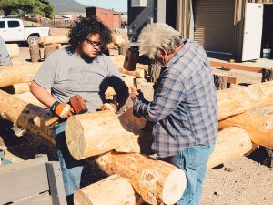 two builders notching logs for a log home