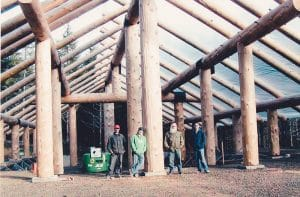crew standing inside the frame of a log construction